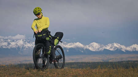 The woman travel on mixed terrain cycle touring with bikepacking. The traveler journey with bicycle bags. Sport tourism bikepacking, bike, sportswear in green black colors. Mountain snow capped. Stockfoto