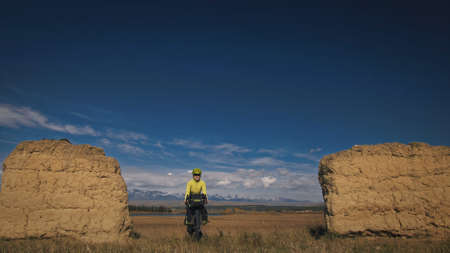The woman travel on mixed terrain cycle touring with bikepacking. The traveler journey with bicycle bags. Sport bikepacking, bike, sportswear in green black colors. Mountain snow capped, stone arch.
