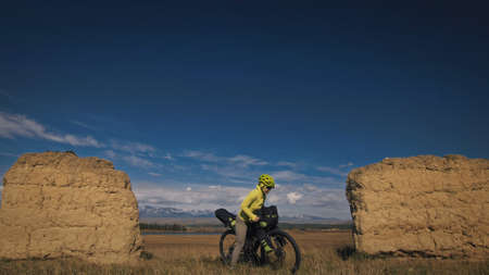 The woman travel on mixed terrain cycle touring with bikepacking. The traveler journey with bicycle bags. Sport bikepacking, bike, sportswear in green black colors. Mountain snow capped, stone arch. Stockfoto