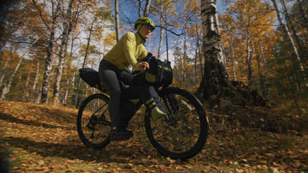 The woman travel on mixed terrain cycle touring with bikepacking. The traveler journey with bicycle bags. Sportswear in green black colors. The trip in magical autumn forest, river stream. Stockfoto