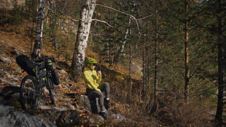 The woman travel on mixed terrain cycle touring with bikepacking. The traveler journey with bicycle bags. Sportswear in green black colors. The trip in magical autumn forest, river stream. Foto de archivo