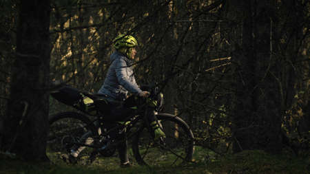 The woman travel on mixed terrain cycle touring with bike bikepacking outdoor. The traveler journey with bicycle bags. Stylish bikepacking, bike, sportswear in green black colors. Magic forest park.