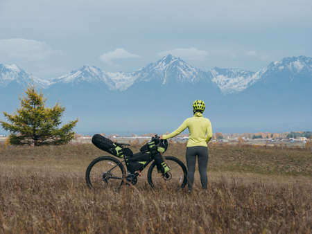 The woman travel on mixed terrain cycle touring with bikepacking. The traveler journey with bicycle bags. Sport tourism bikepacking, bike, sportswear in green black colors. Mountain snow capped.