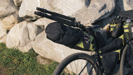 The mixed terrain cycle touring bike with bikepacking. The travel journey with light bicycle bags designed or modified for cycling. The trip on multitrack bike, outdoor road in mountain snow capped. Stockfoto