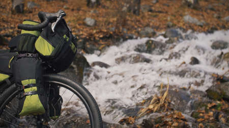 The mixed terrain cycle touring bike with bikepacking. The travel journey with light bicycle bags designed or modified for cycling. The trip on bike, outdoor in magical autumn forest, river stream.