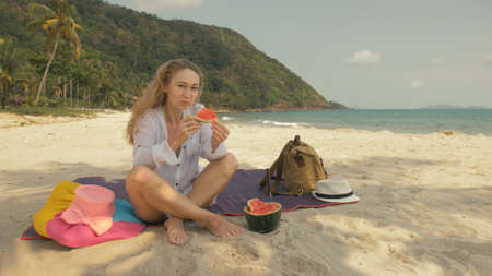 The cheerful woman holding and eating slices of watermelon on tropical sand beach sea. Portrait attractive beautiful girl caucasian spend summer weekend in outdoor. White shirt beachwear.