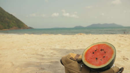 Fresh juicy watermelon on a background of a sandy beach and the sea. Close up. Stockfoto
