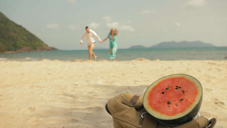 The cheerful love couple in blur, against the background of a watermelon on tropical sand beach sea. Romantic lovers two people caucasian spend summer weekend in outdoor. White shirt beachwear.