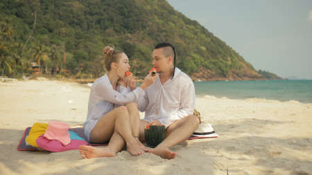 The cheerful love couple holding and eating slices of watermelon on tropical sand beach sea. Romantic lovers two people caucasian spend summer weekend in outdoor. Hat, backpack white shirt beachwear.