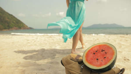 The cheerful woman in blur, against the background of a watermelon on tropical sand beach sea. Portrait attractive beautiful girl caucasian spend summer weekend in outdoor. White shirt beachwear. Stockfoto