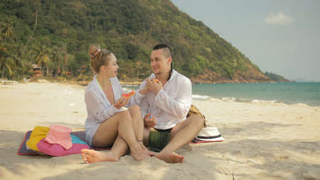 The cheerful love couple holding and eating slices of watermelon on tropical sand beach sea. Romantic lovers two people caucasian spend summer weekend in outdoor. Hat, backpack white shirt beachwear. Imagens