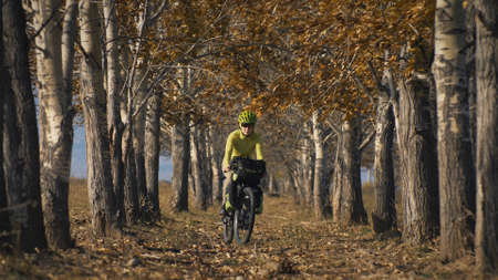 The woman travel on mixed terrain cycle touring with bikepacking. The traveler journey with bicycle bags. Sportswear in green black colors. The trip in magical autumn forest, arch, alley, avenue.