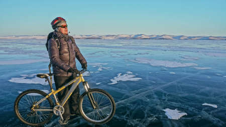 Man is riding bicycle on the ice. Ice of the frozen Lake Baikal. Rider is dressed in black down jacket, cycling backpack, helmet. Tires on covered with special spikes. Traveler boy is ride cycle.