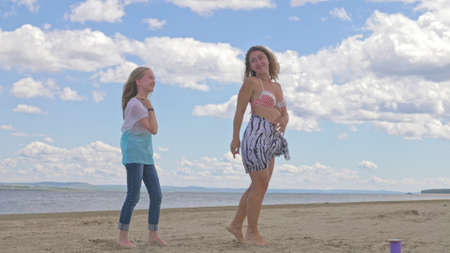 The family dances on the beach. They are not professional dancers. They are fun and they are funny. In video a mother and daughter.
