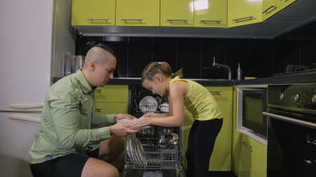 Father teaching daughter smart girl learning to use dishwasher. Stylish modern Built In Kitchen Appliances in green black. Young mistress children loading putting dirty dishes in automatic dishwasher.