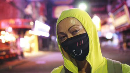 Woman close up look caucasian at Pattaya Walking Street with wearing protective medical mask.