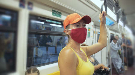 Woman travel caucasian ride at overground train airtrain with wearing protective medical red mask. Girl tourist at airtrain with respirator.