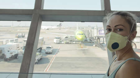 Woman caucasian at airport with wearing protective medical mask on head against the background of the plane. 写真素材