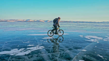 Man is riding bicycle on the ice. Ice of the frozen Lake Baikal. Rider is dressed in black down jacket, cycling backpack, helmet. Tires on covered with special spikes. Traveler boy is ride cycle. 写真素材