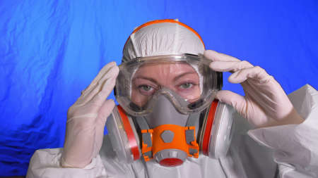 Scientist virologist in respirator. Slow motion. Woman close up look wearing protective medical mask.