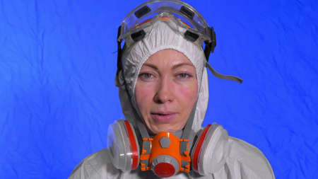 Scientist virologist in respirator. Slow motion. Woman close up look wearing protective medical mask. Concept health safety N1H1 virus protection  epidemic 2019 nCoV. Chroma key blue film.