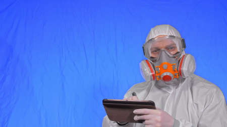 Scientist virologist in respirator makes write in an tablet computer with stylus. Man wearing protective medical mask.