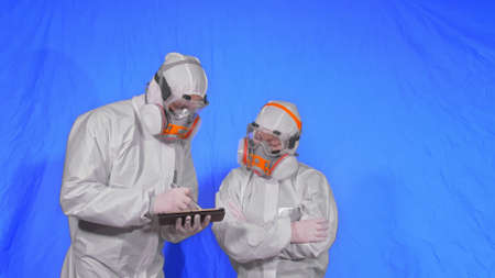 Scientist virologist in respirator makes write in an tablet computer with stylus. Man and woman wearing protective medical mask. 写真素材