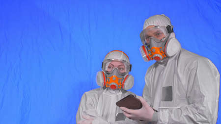 Scientist virologist in respirator makes write in an tablet computer with stylus. Man and woman wearing protective medical mask.