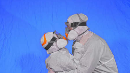 Doctor man and woman in protective costume suit, gas protect medical spray paint mask. Love couple kiss and hug, health worker in respirator.