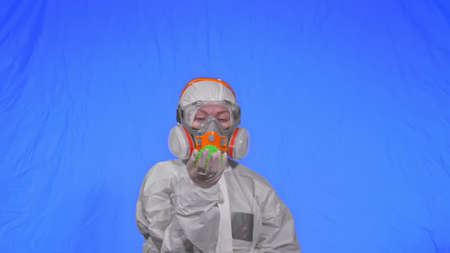 Doctor in respirator show a virus model concept health safety protection   epidemic 2019 nCoV. Slow motion. Woman wearing protect medical aerosol spray paint mask. Green ball spike thorn.