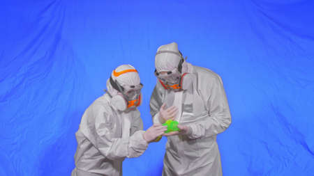Doctor in respirator show a virus model concept health safety protection  epidemic 2019 nCoV. Slow motion. Health worker wearing protect medical aerosol spray paint mask. Green ball spike.