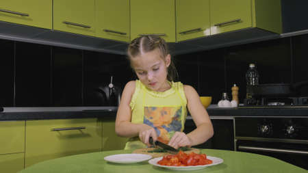 Smart girl learning to cook. Happy and serious young mistress children to cook a Neapolitan egg fried omelette from sausage. Modern Built In Kitchen Appliances in green black color. Cut tomato dill. 写真素材