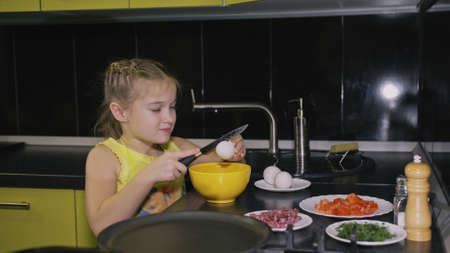 Smart girl learning to cook. Happy and serious young mistress children to cook a Neapolitan egg fried omelette from sausage. Modern Built In Kitchen Appliances in green black color. 写真素材