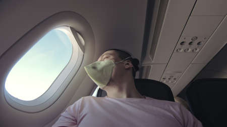 Man travel caucasian at plane with wearing protective medical mask. Male tourist at aircraft with protect respirator. 写真素材