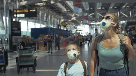 Woman and child baby tourist caucasian at airport with wearing protective medical mask. Family in quarantine isolation.