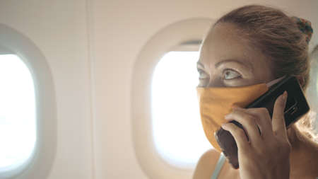 Woman travel tourist caucasian at plane aircraft with wearing protective medical mask. Girl talking about coronovirus on phone smartphone mobile. 写真素材