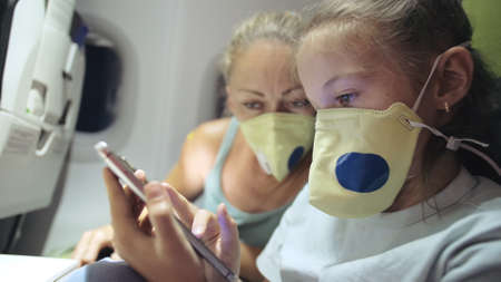 Family woman and child baby travel tourist caucasian at plane aircraft with wearing protective medical mask. Use smartphone mobile.