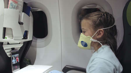 Little girl caucasian at plane with wearing protective medical mask. Child baby tourist at aircraft with respirator play at smartphone mobile phone. 写真素材
