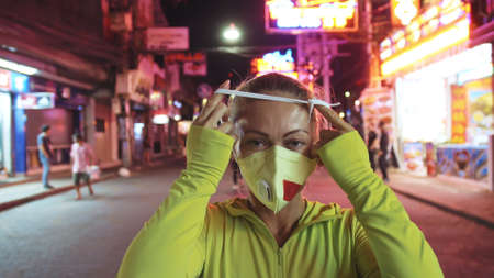 Woman close up look caucasian at Pattaya Walking Street with wearing protective medical mask. Lockdown quarantine isolation. 写真素材