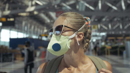 Woman caucasian at Suvarnabhumi Airport with wearing protective medical mask on head against background of plane.