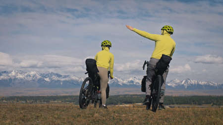 The man and woman travel on mixed terrain cycle touring with bikepacking. The love couple journey with tent in nature with bicycle bags. Stylish bikepacking, bike, sportswear in green black colors.
