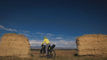 The man travel on mixed terrain cycle touring with bikepacking. The traveler journey with bicycle bags. Sport bikepacking, bike, sportswear in green black colors. Mountain snow capped, stone arch. Stock fotó