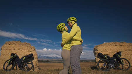 The man and woman travel on mixed terrain cycle touring with bikepacking. The two people journey with bicycle bags. Mountain snow capped, stone arch. Foto de archivo