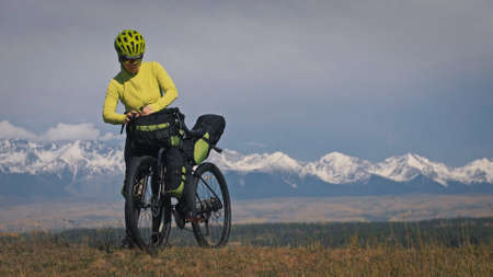 The woman travel on mixed terrain cycle touring with bikepacking. The traveler journey with bicycle bags. Sport tourism bikepacking. Foto de archivo