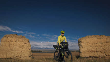 The woman travel on mixed terrain cycle touring with bikepacking. The traveler journey with bicycle bags. Sport tourism bikepacking. Archivio Fotografico