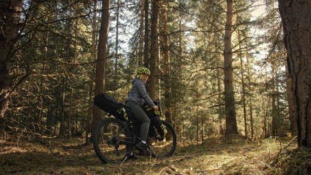 The woman travel on mixed terrain cycle touring with bike bikepacking. The traveler journey with bicycle bags. Magic forest park. Stock fotó