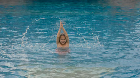 The little cute girl have fun in the pool. The child enjoy summer vacation in a swimming pool jumping, spinning, splash water. Happy childhood.