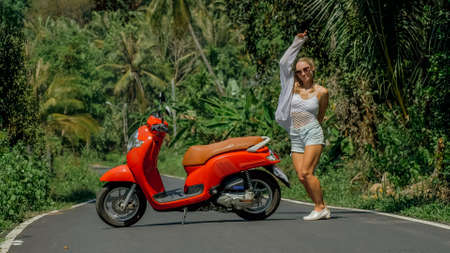 Woman on red scooter in white clothes drive on forest road trail. Dancing trip. One girl caucasian tourist in sunglasses dance, relax near motorbike.