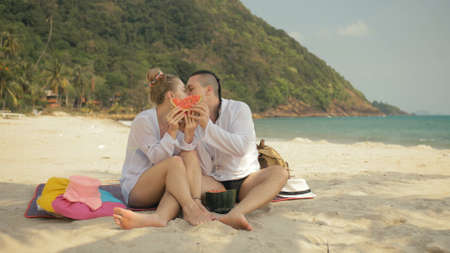 The cheerful love couple holding and eating slices of watermelon on tropical sand beach sea. Romantic lovers two people spend summer weekend.