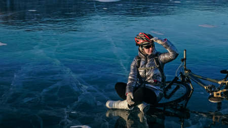 Woman sitting near her bike on ice. The girl cyclist stopped to